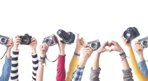Mãos diferentes da cor que guardam câmeras fotografia de stock royalty free