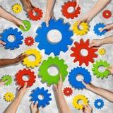 Mãos diversas que guardam as engrenagens coloridas Fotografia de Stock Royalty Free