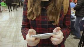 Mãos do adolescente fêmea viciado ao jogo que joga no smartphone na multidão video estoque