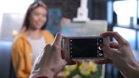 Mãos do amigo que tomam fotos do pintor da mulher vídeos de arquivo