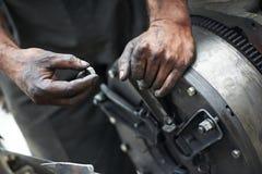 Mãos do auto mecânico no trabalho do reparo do carro
