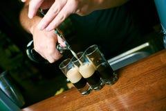 mãos do barman que derramam um cocktail fotografia de stock