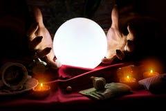 Mãos do caixa de fortuna com bola de cristal no meio fotos de stock