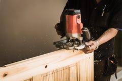 Mãos do carpinteiro com o formão nas mãos Fotos de Stock