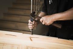 Mãos do carpinteiro com o formão nas mãos Foto de Stock