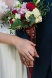 Mãos do casal com anéis e ramalhete do casamento fotografia de stock royalty free