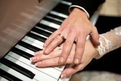 Mãos do casamento dois em chaves do piano Imagens de Stock Royalty Free