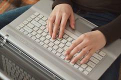 Mãos do close up da moça bonita que encontram-se na cama e que usam o computador em casa imagem de stock royalty free