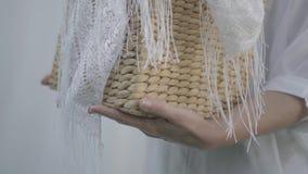 Mãos do close-up da mulher madura que guardam a cesta de vime ao pendurar a roupa branca em uma corda fora washday filme