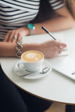 Mãos do close-up da mulher que guardam uma pena sobre o caderno vazio com a xícara de café ao lado dela Composição da vista super fotografia de stock