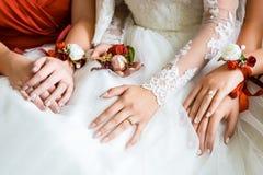 Mãos do close up da noiva e das damas de honra Foto de Stock