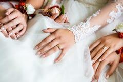 Mãos do close up da noiva e das damas de honra Imagens de Stock