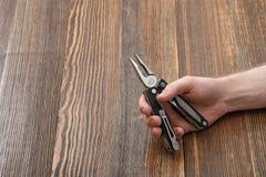 Mãos do close-up do homem que guardam o multitool em um fundo de madeira Fotos de Stock Royalty Free