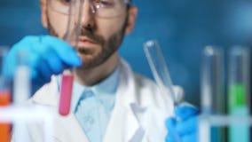 Mãos do close-up do químico profissional que derramam a taça de utilização reativa líquida no laboratório filme