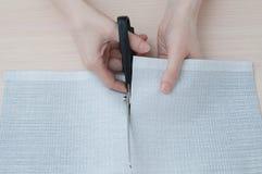 Mãos do close up que cortam o pano com tesouras fotografia de stock