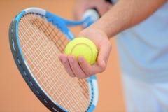 Mãos do close up que mantêm a raquete e a bola de tênis poised para servir Foto de Stock