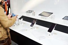 Mãos do comprador com os smartphones móveis na loja da eletrônica imagem de stock