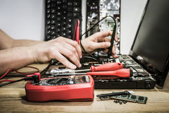Mãos do coordenador eletrônico que reparam o portátil quebrado fotos de stock royalty free