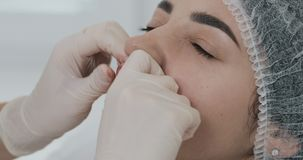 Mãos do cosmetologist que faz massagens os bordos do paciente após o aumento do bordo Fim acima vídeos de arquivo
