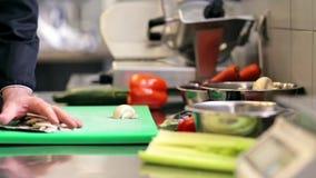 Mãos do cozinheiro chefe masculino que desbastam cogumelos na cozinha video estoque