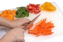 Mãos do cozinheiro chefe que cortam vegetais Fotos de Stock Royalty Free