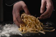 Mãos do cozinheiro chefe que fazem os espaguetes, massa, macarronetes com massa fresca na tabela preta com fotos de stock royalty free