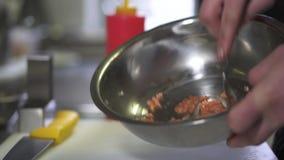 Mãos do cozinheiro chefe que misturam salmões triturados com a colher do te no fim de alumínio grande da bacia acima Preparação d filme