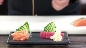 Mãos do cozinheiro chefe que preparam o sashimi filme