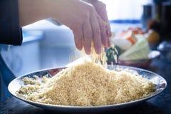 Mãos do cozinheiro chefe que preparam a placa marroquina tradicional do cuscuz fotos de stock royalty free
