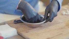 Mãos do cozinheiro nas luvas de borracha pretas que preparam o alimento especial no fim de alumínio da bacia acima na cozinha do  filme