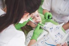 Mãos do dentista pediatra irreconhecível e do procedimento de fatura assistente do exame para a menina bonito de sorriso foto de stock royalty free