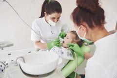 Mãos do dentista pediatra irreconhecível e do procedimento de fatura assistente do exame para a menina bonito de sorriso fotografia de stock royalty free