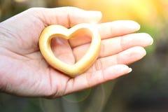 Mãos do dia de Valentim da pessoa que guardam o coração de madeira sob o sunl Fotografia de Stock Royalty Free