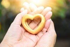 Mãos do dia de Valentim da pessoa que guardam o coração de madeira sob o sunl Imagens de Stock Royalty Free