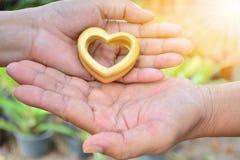 Mãos do dia de Valentim da pessoa que guardam o coração de madeira sob o sunl Imagem de Stock Royalty Free