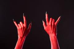 Mãos do diabo vermelho que mostram o metal pesado Fotografia de Stock Royalty Free