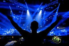 Mãos do DJ acima no partido do clube noturno sob a luz azul com a multidão de povos fotografia de stock