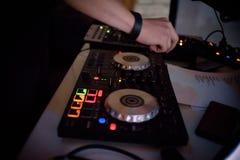 Mãos do DJ na plataforma e no misturador do equipamento com registro de vinil no partido Foto de Stock