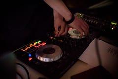Mãos do DJ na plataforma e no misturador do equipamento com registro de vinil no partido Fotografia de Stock Royalty Free