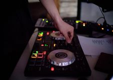 Mãos do DJ na plataforma e no misturador do equipamento com registro de vinil no partido Fotos de Stock Royalty Free