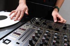 Mãos do DJ que riscam o registro de vinil fotografia de stock