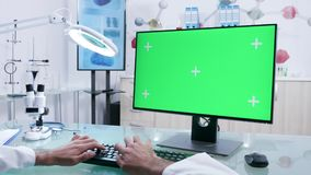 Mãos do doutor que datilografam na zombaria do computador acima da tela verde filme