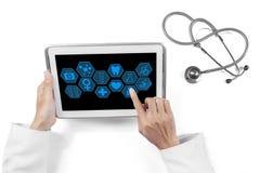 Mãos do doutor usando ícones médicos na tabuleta Fotografia de Stock Royalty Free