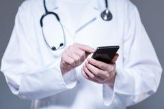 Mãos do doutor usando o telefone celular Imagem de Stock Royalty Free