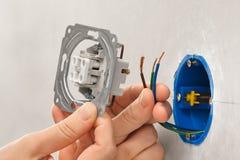 Mãos do eletricista que instalam o interruptor da luz na placa de gesso wal foto de stock