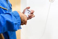 Mãos do eletricista que instalam a parede elétrica Fotografia de Stock