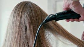 Mãos do estilista com o secador de cabelo que seca o cabelo fêmea reto longo no salão de beleza video estoque