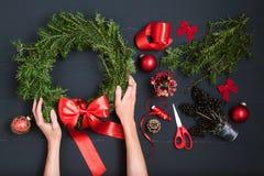 Mãos do florista que fazem a grinalda do Natal Fotografia de Stock