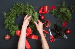Mãos do florista que fazem a grinalda do Natal Imagens de Stock Royalty Free