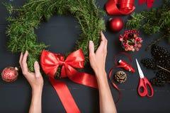 Mãos do florista que fazem a grinalda do Natal Foto de Stock